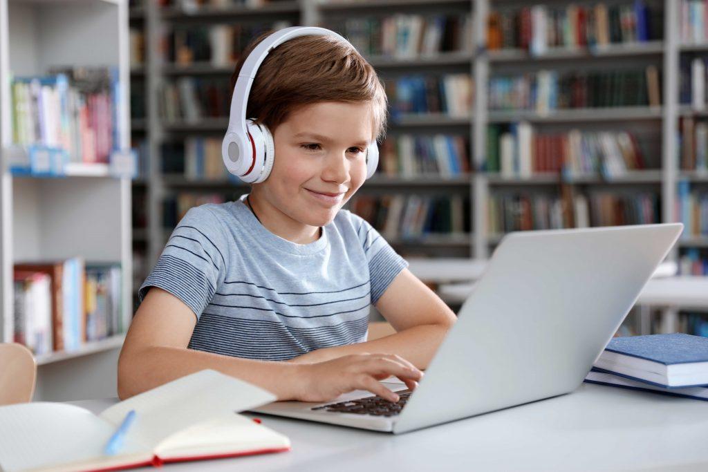 Pojke med dator och hörlurar